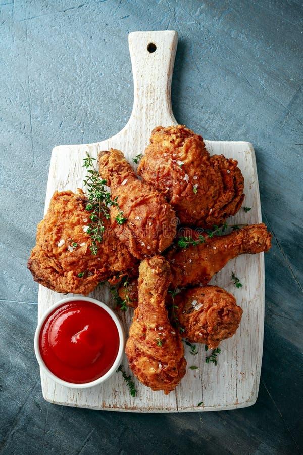 Jambes de poulet croustillantes frites, cuisse sur la planche à découper blanche avec le ketchup et herbes photographie stock libre de droits