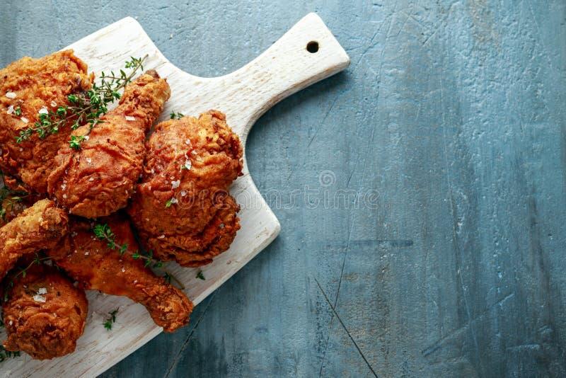 Jambes de poulet croustillantes frites, cuisse sur la planche à découper blanche avec le ketchup et herbes image libre de droits