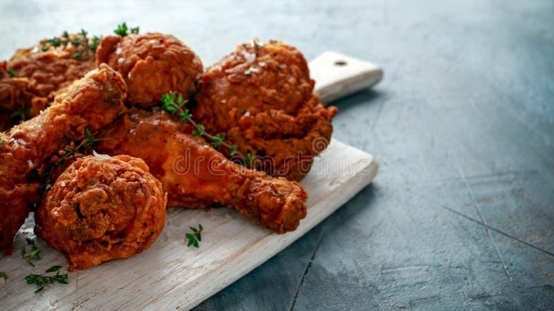 Jambes de poulet croustillantes frites, cuisse sur la planche à découper blanche avec le ketchup et herbes images libres de droits