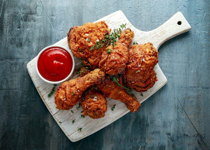 Jambes de poulet croustillantes frites, cuisse sur la planche à découper blanche avec le ketchup et herbes images stock