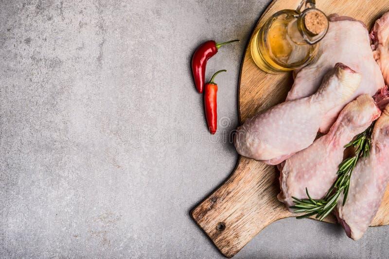 Jambes de poulet crues sur la planche à découper pour faire cuire sur le fond concret gris images stock