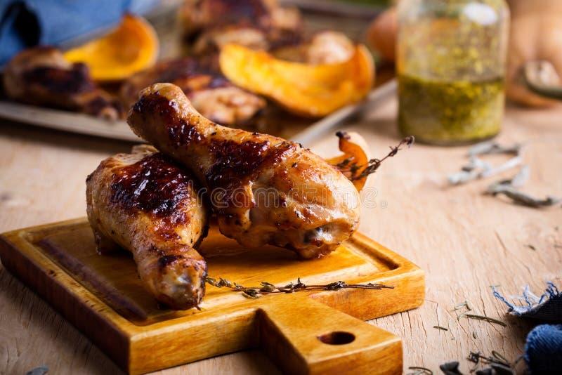 Jambes de poulet cuites au four avec la courge de butternut et l'herbe de thym images stock