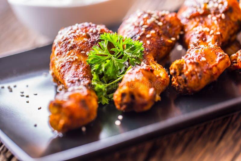 Jambes de poulet de gril BBQ grillé de jambes de poulet avec le persil et la tomate de sésame photos stock