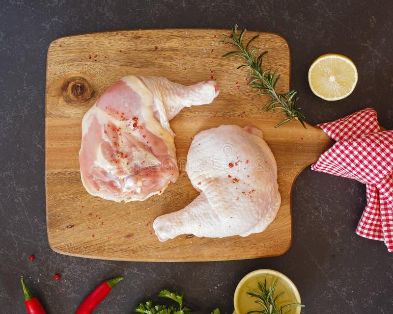 Jambes de poulet et cuisses crues sur un hachoir photo stock
