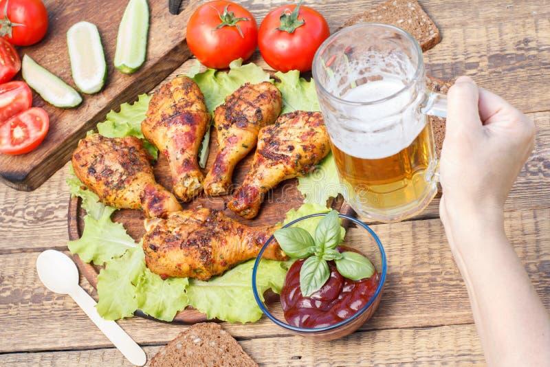Jambes de poulet et feuilles grillées de laitue sur le hachoir en bois image libre de droits