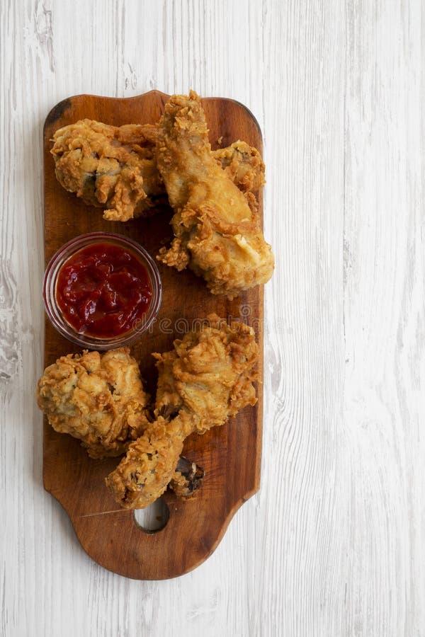 Jambes de poulet frit avec de la sauce sur le conseil en bois au-dessus de la surface en bois blanche, vue aérienne Configuration photo libre de droits
