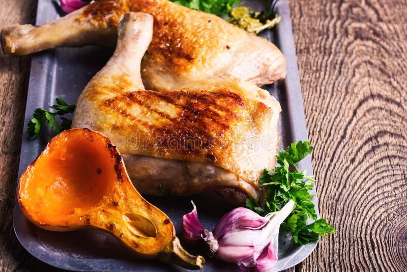 Jambes de poulet grillées, potiron rôti, sauce à pesto et persil frais image libre de droits