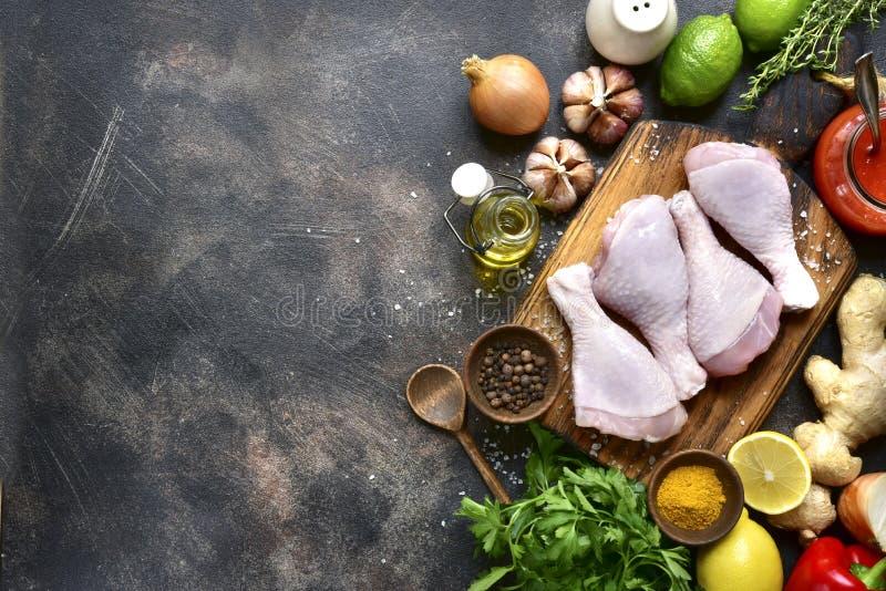 Jambes de poulet organiques crues avec des ingrédients pour faire cuire le marinatin photographie stock