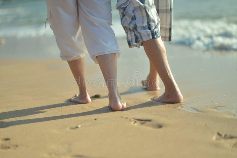 Jambes des couples sur une plage image libre de droits
