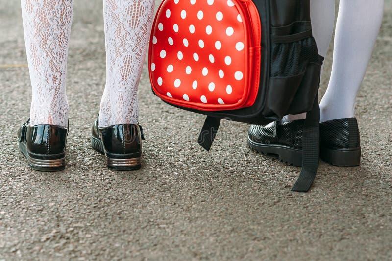 Jambes des filles dans l'uniforme scolaire avec un sac à dos sur le fond de l'asphalte De nouveau au concept d'?cole photo stock