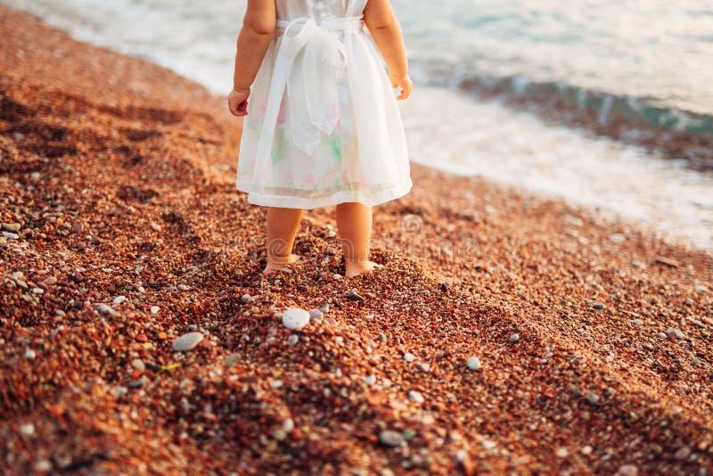 Jambes du ` s d'enfants et pieds de parents La famille marche le long de la plage images libres de droits
