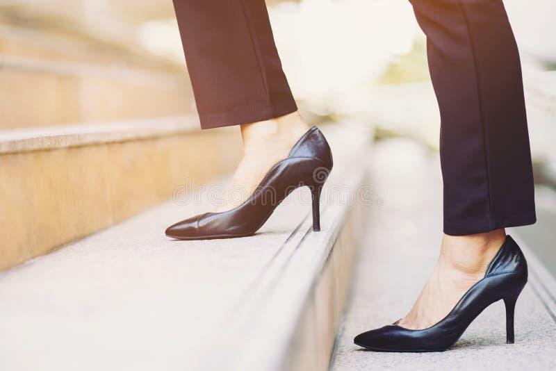 Jambes en gros plan modernes de travailleuse active de femme d'affaires marchant vers le haut des escaliers dans la ville moderne photos libres de droits