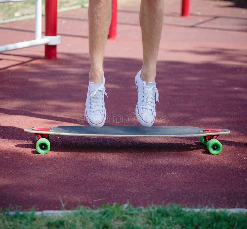 Jambes en gros plan sur une planche à roulettes Équipez la position sur un longboard à la mode sur un fond brouillé de parc Conce photographie stock libre de droits