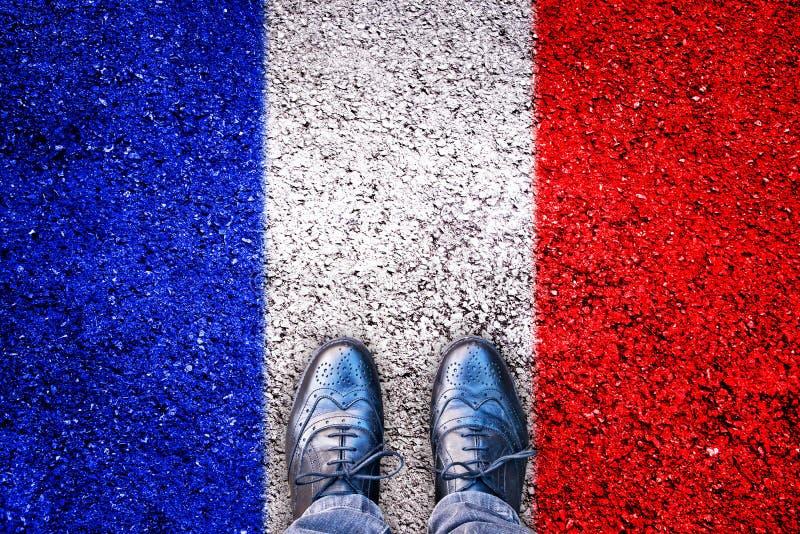Jambes et chaussures sur l'asphalte avec le drapeau français photos stock