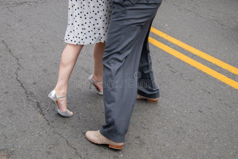 Jambes et pieds de couples masculins et femelles démontrant des mouvements de danse sur la rue photographie stock libre de droits
