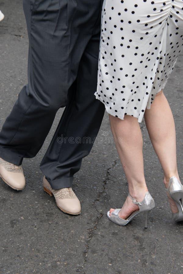 Jambes et pieds de couples masculins et femelles démontrant des mouvements de danse sur la rue photo libre de droits