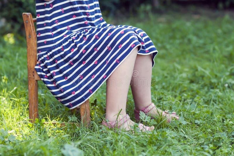 Jambes et pieds de petite fille dans la robe se reposant sur une chaise sur le gree images libres de droits