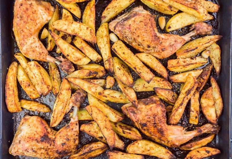 Jambes et pommes de terre de poulet croquantes avec l'assaisonnement épicé et le Garl photographie stock libre de droits