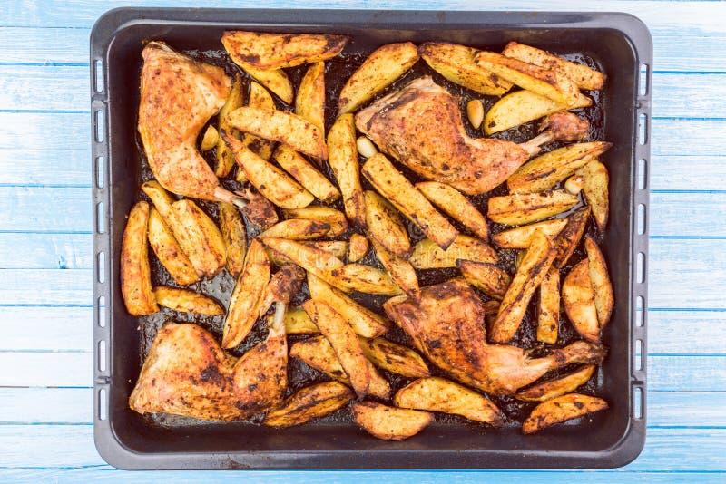 Jambes et pommes de terre de poulet croquantes avec l'assaisonnement épicé et le Garl photographie stock
