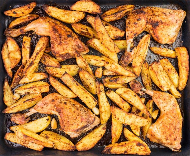 Jambes et pommes de terre de poulet croquantes avec l'assaisonnement épicé et le Garl photos stock