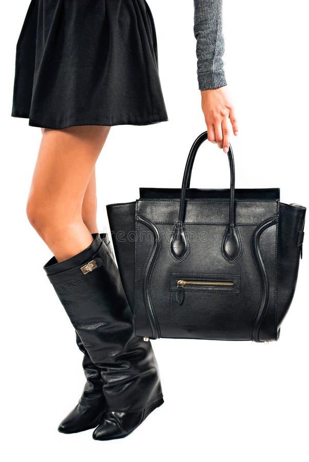 Jambes femelles avec les bottes noires et une pousse de sac dans le studio sur le fond blanc image stock