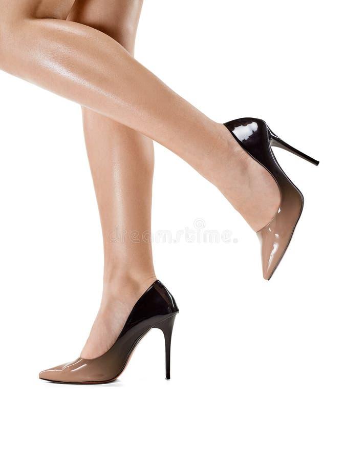 Jambes femelles bronzées dans des talons hauts d'isolement sur le fond blanc photo stock