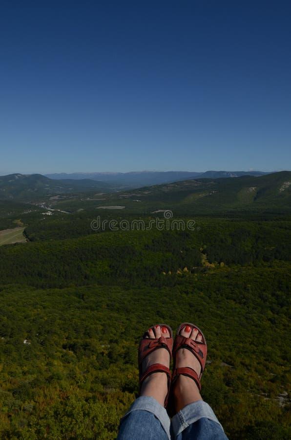 Jambes femelles dans des chaussures de trekking au-dessus d'un précipice énorme sur un fond de forêt verte et de ciel bleu crimea photographie stock