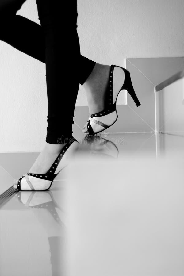 Jambes femelles dans des talons hauts descendant des escaliers, noirs et blancs photo libre de droits