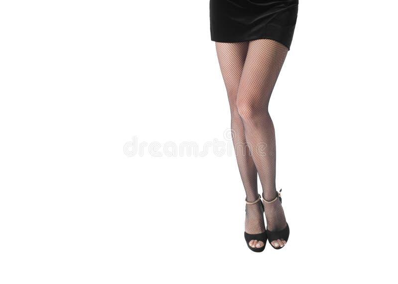 Jambes femelles dans le collant noir de filet et hautes des chaussures gîtées, d'isolement sur le blanc photo stock
