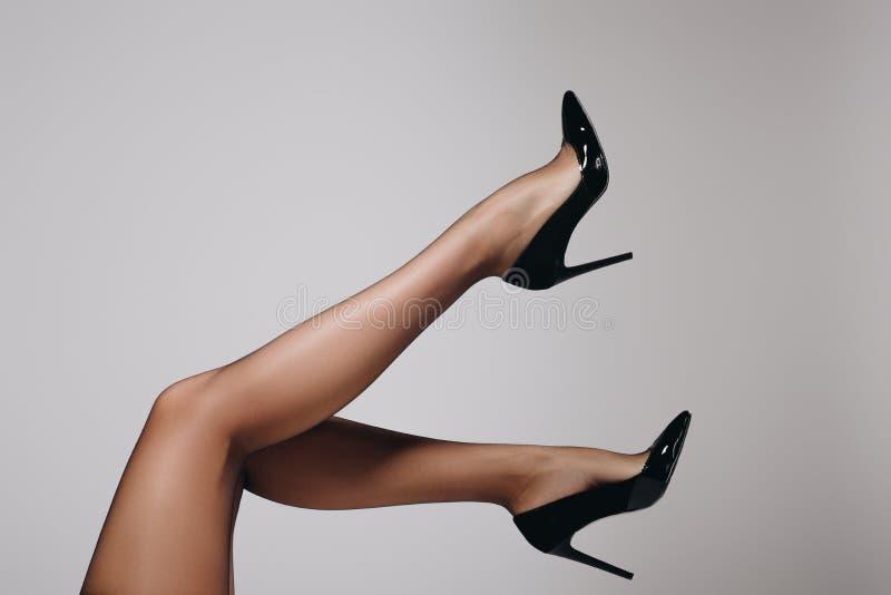 Jambes femelles dans les bas et des chaussures noirs de talon images stock