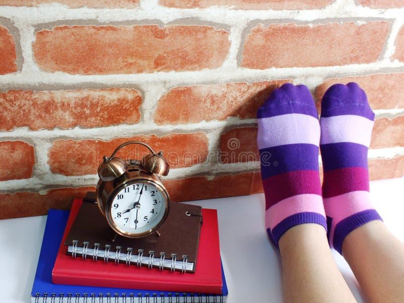 Jambes femelles dans les chaussettes colorées avec le carnet et le réveil photographie stock libre de droits