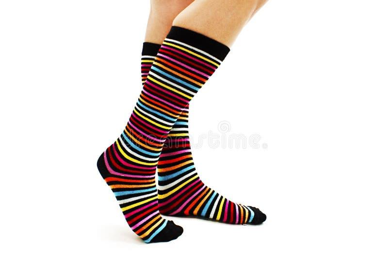 Jambes femelles dans les chaussettes rayées colorées photographie stock
