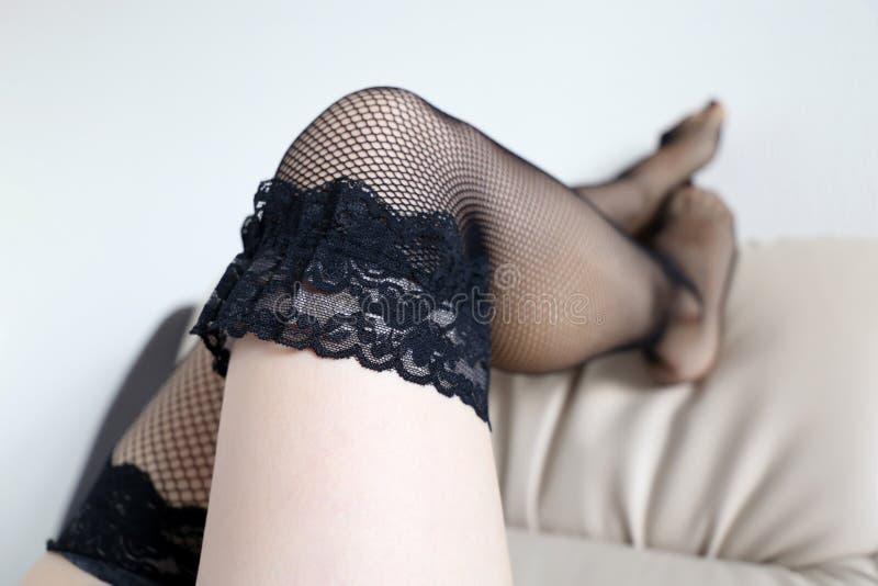 Jambes femelles parfaites dans les bas noirs de filet photographie stock libre de droits