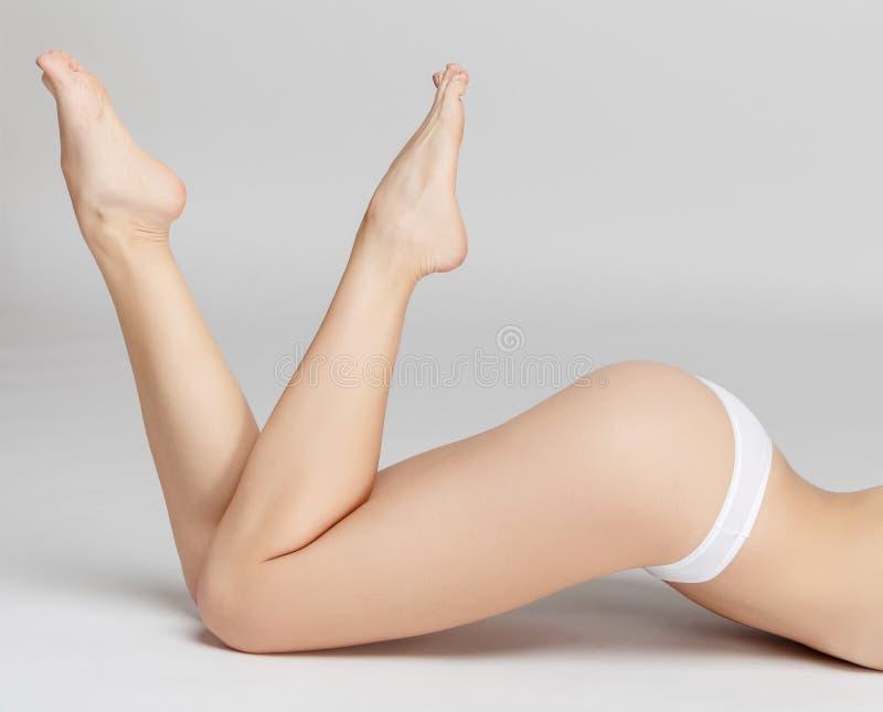 Jambes femelles parfaites sur le fond gris photos stock