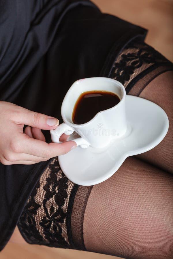 Jambes femelles sexy avec la tasse de café photographie stock