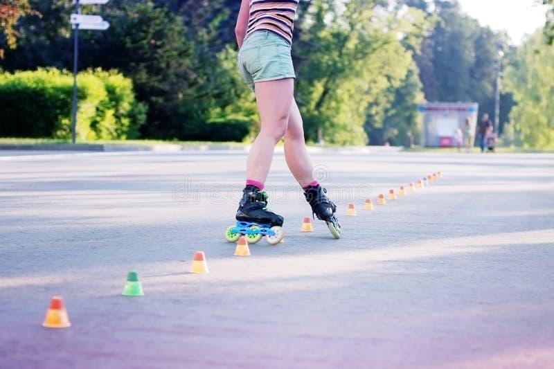 Jambes fortes de femme de patineur de rouleau dans le mouvement photographie stock