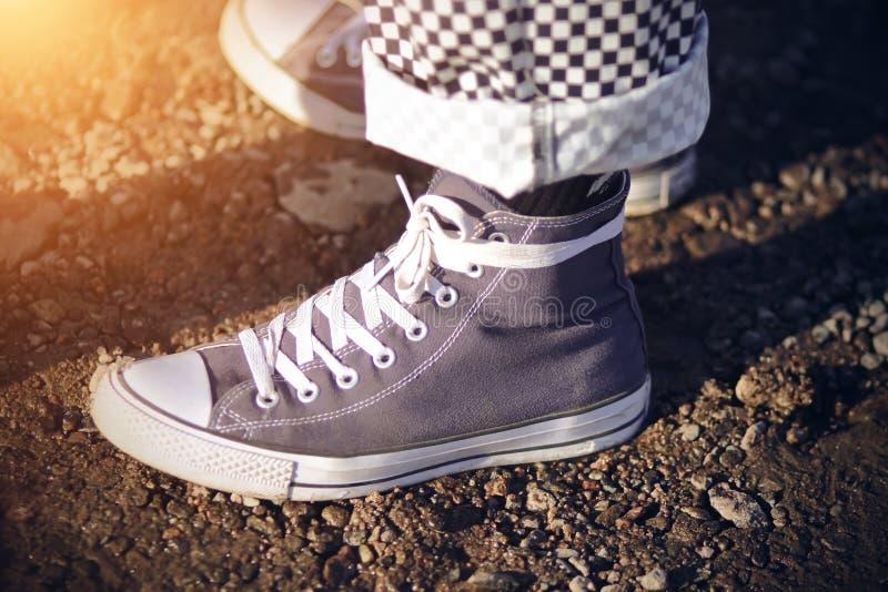 Jambes, habillées dans des vêtements à la mode se tenant au sol boueux humide photos stock