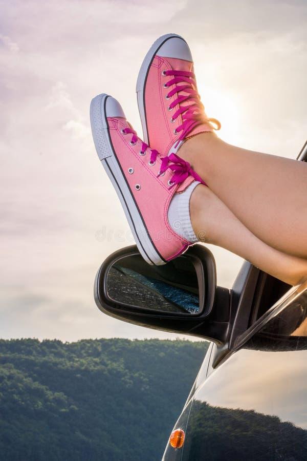 Jambes hors de la fenêtre de voiture par le lac photo libre de droits
