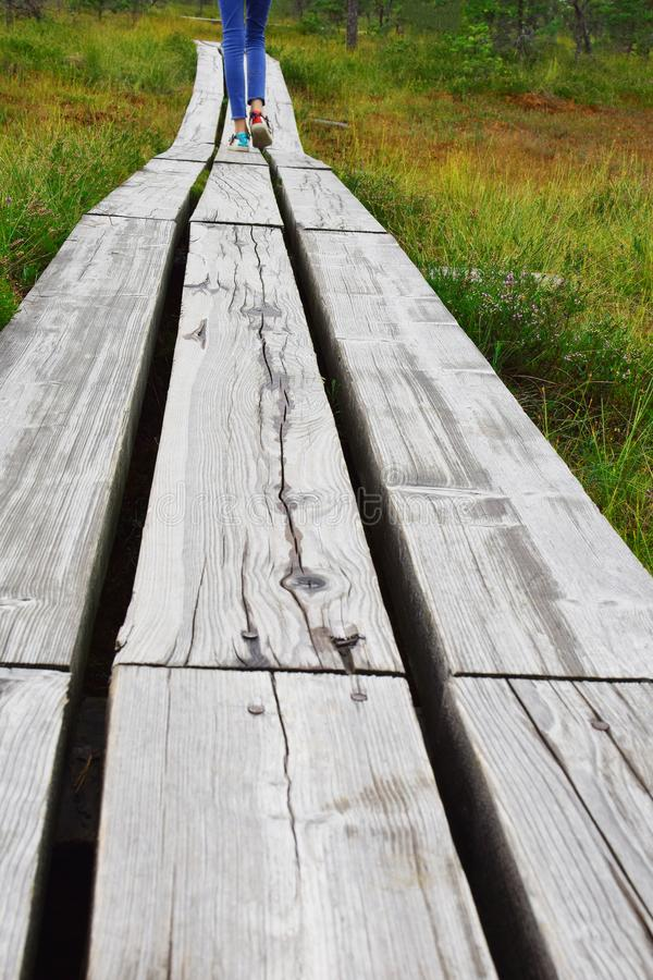 Jambes marchant loin sur la voie en bois photos stock