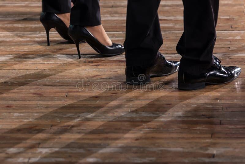 Jambes masculines et femelles dans les chaussures et des pantalons noirs sur un vieux plancher de parquet en bois Plan rapproché photos libres de droits