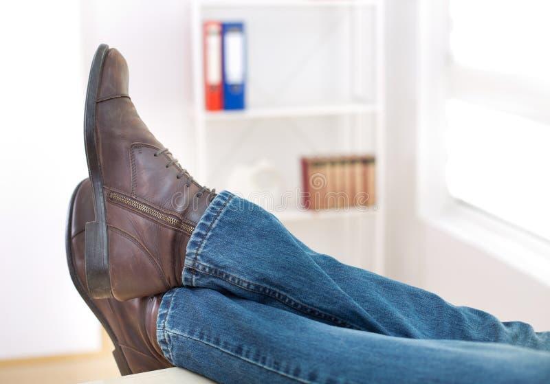 Jambes masculines sur le bureau photo libre de droits