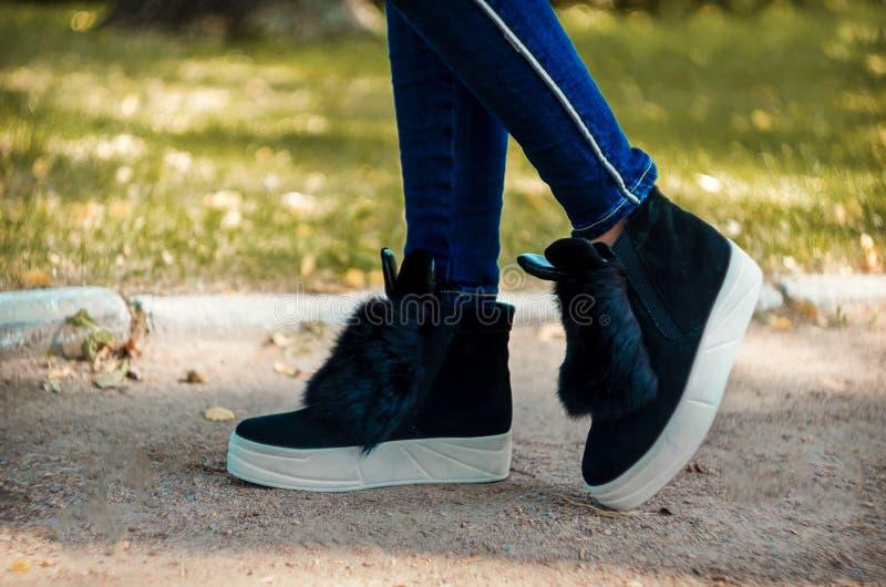 Jambes minces dans des jeans chaussés dans des bottes de tendance avec la fourrure et les oreilles sur une semelle épaisse blanch photographie stock