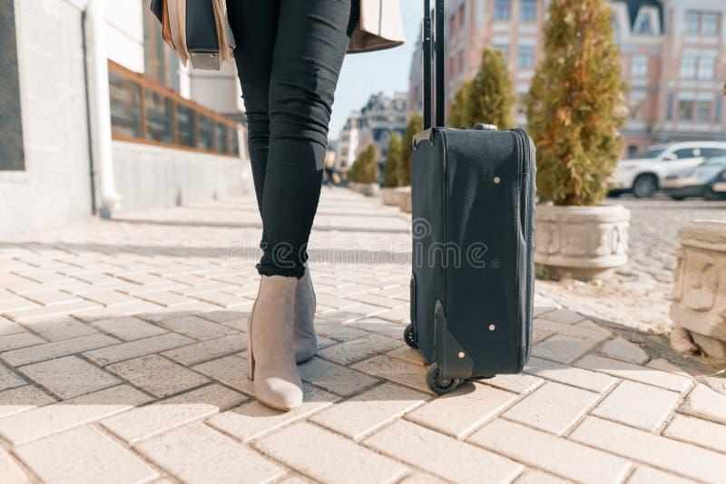 Jambes noires de touristes de valise et de femme sur une rue de ville photo libre de droits