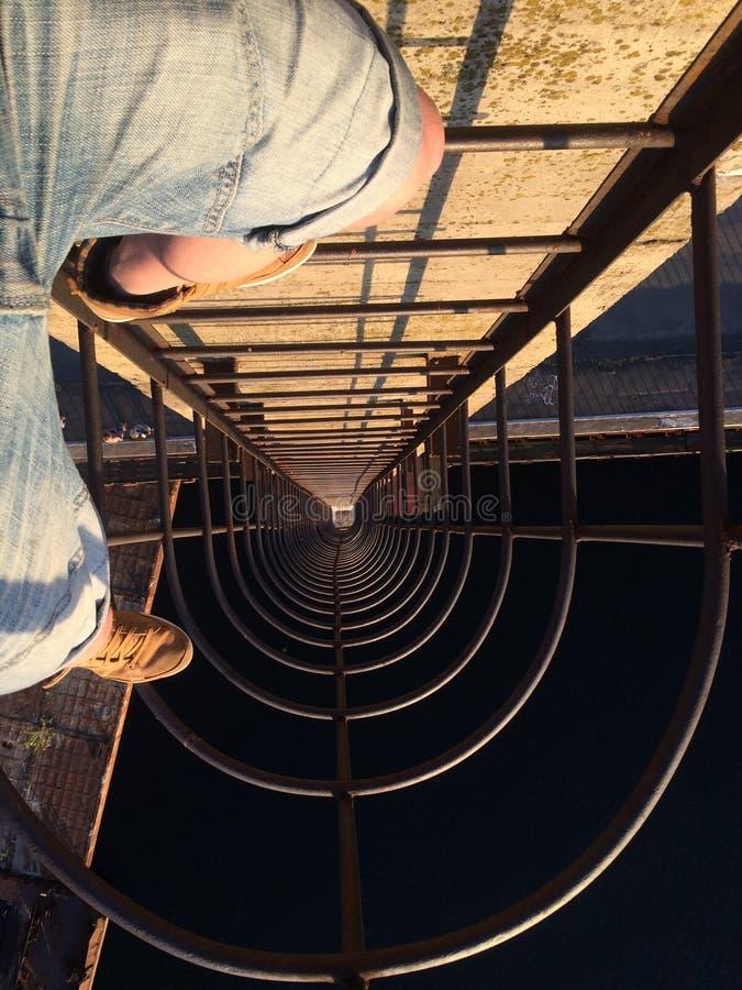 Jambes se tenant sur l'échelle sur le haut pont près de la mer de rivière photos libres de droits