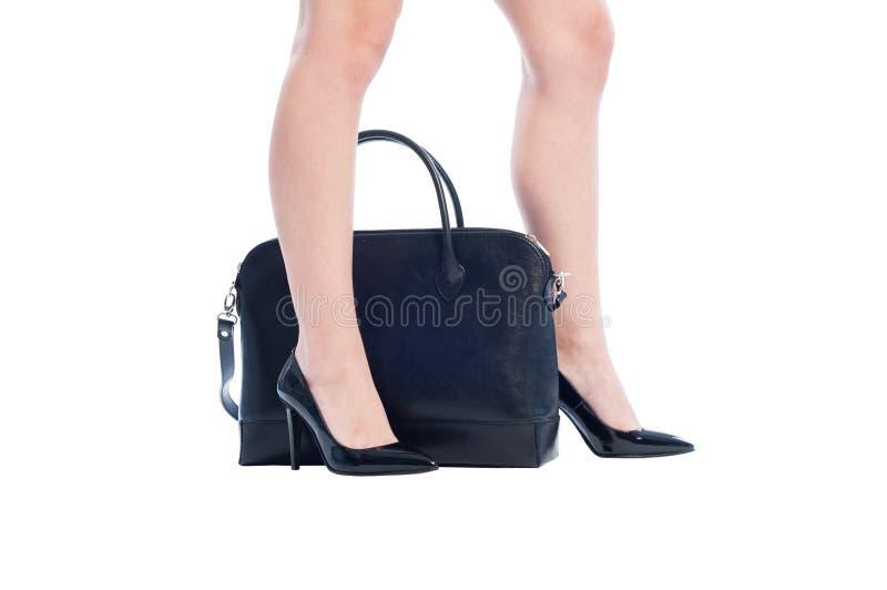 Jambes sexy de femme d'affaires avec les chaussures et le sac à main noirs photos stock