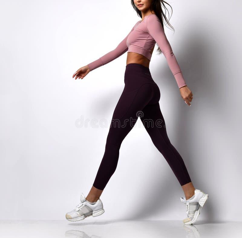 Jambes sportives de femme marchant dans l'usage de sport sur un blanc photos libres de droits