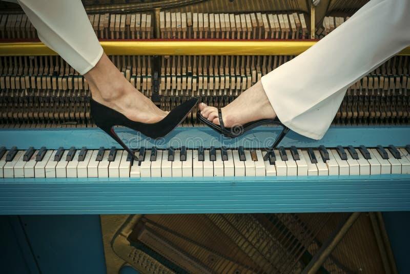 Jambes sur la couleur bleue de clavier de piano, mode photos libres de droits