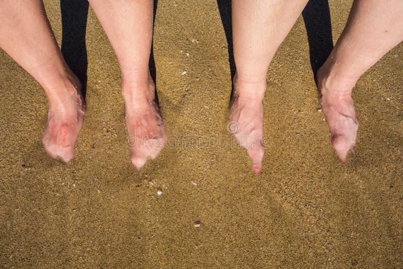 Jambes sur une plage sablonneuse en Palma de Mallorca, Espagne images libres de droits