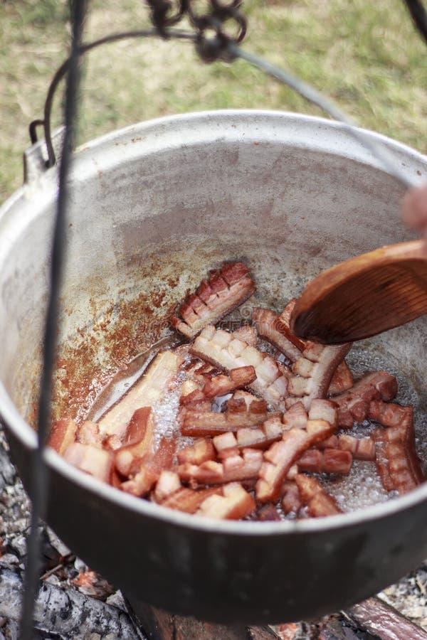 Jambières de porc Graisse de porc fondant dans un pot à cuire dehors photo libre de droits