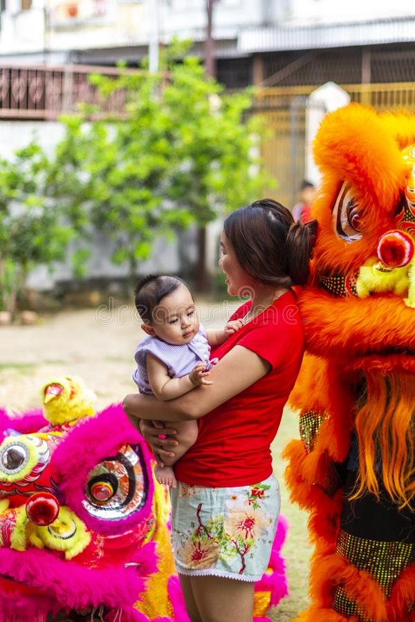 Jambi, Indonesia - January 28, 2017: Happy Asian mother holding baby posing next to lion dance performers doing acrobatics. To celebrate Chinese new year royalty free stock photo